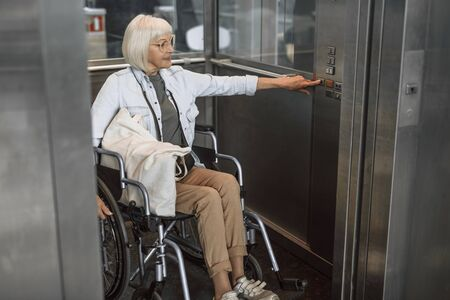Photo pour Mature woman in glasses on disabled carriage using elevator - image libre de droit