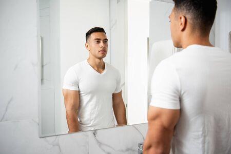 Photo pour Back side portrait of young man looking at mirror - image libre de droit