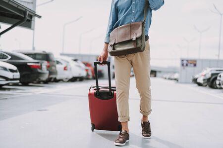 Photo pour Young guy walking on the parking lot with bag outdoors - image libre de droit