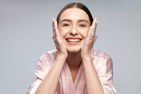 Photo for Cheerful pretty girl washing face with foaming cleanser - Royalty Free Image