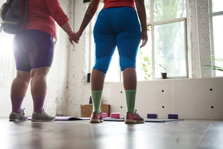 Photo pour Cropped photo of fat ladies going to work out in gym - image libre de droit