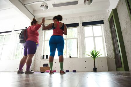 Photo pour Two female friends are ready for sport exercises in gym - image libre de droit