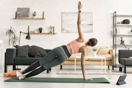 Foto de Female practicing side plank at home stock photo - Imagen libre de derechos