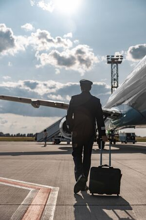Photo pour Adult pilot hurrying for the flight at airport - image libre de droit
