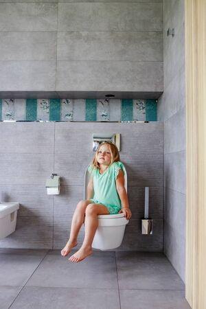 Foto de Cute girl is sitting in the toilet - Imagen libre de derechos