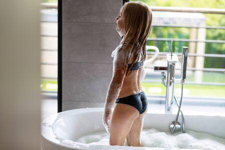 Photo pour Girl in bathing suit standing in bath - image libre de droit