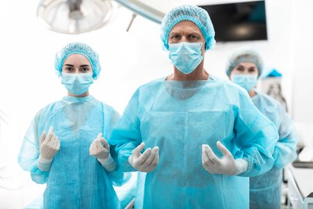 Photo pour Surgeon and his assistants in sterile blue gowns standing in operating room - image libre de droit