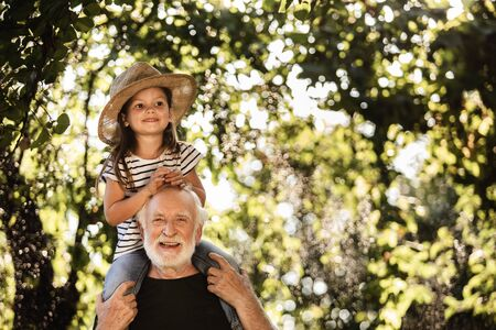 Photo pour Little girl with old man having fun in garden - image libre de droit