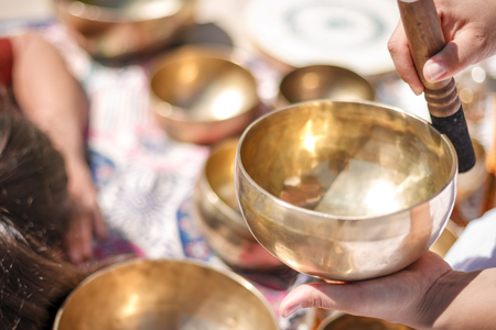 Photo for Woman playing a singing bowls also known as Tibetan Singing Bowls, Himalayan bowls. Making sound massage at beautiful sunny day. - Royalty Free Image