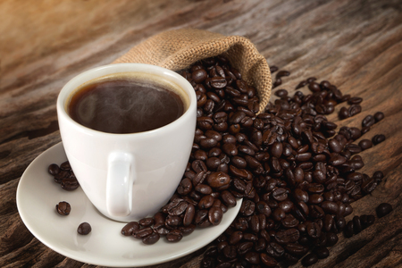 Foto per A cup of hot coffee on a wooden table with roasted coffee beans - Immagine Royalty Free
