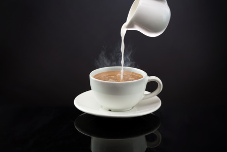 Photo pour Pouring into a hot coffee or tea with steam on black background - image libre de droit