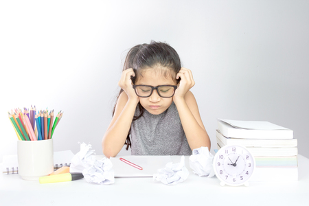 Foto de Stressed young asian girl with her head in hands looking homework and crumpled Paper on the desk - Imagen libre de derechos