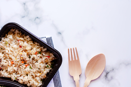 Photo pour Delicious fried rice in lunch box with napery, wooden spoon and fork on marble background for ready to eat and food concept - image libre de droit