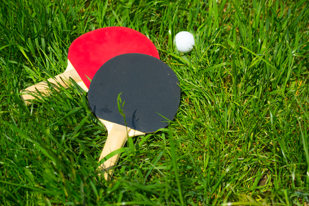Red tennis table paddles with wooden handles lie on the green grass. Play table tennis