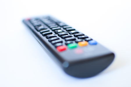 Photo for especially heavily blurred black remote controls for the TV on a white background, closeup - Royalty Free Image