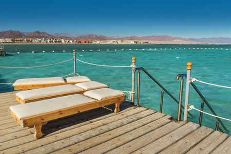 Foto de Pier with chaise longues in the sea in resort. Summer vacation. View at a clear sea with turquoise water. Summer vacation at a sea coastline in an exotic country. Staircase to the water for swimming. - Imagen libre de derechos