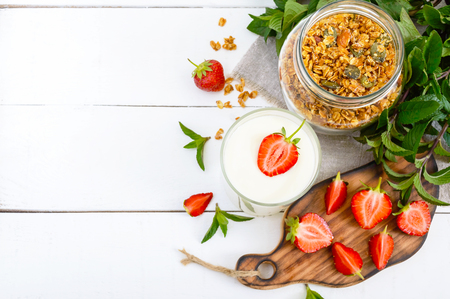 Photo for Yogurt, fresh ripe strawberry, granola - dietary dish on a white wooden table. Proper nutrition. Healthy breakfast. - Royalty Free Image