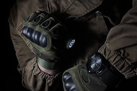 Foto per Photo of a male person in brown tactical outfit jacket and gloves using green tactical led flashlight and military watch. - Immagine Royalty Free