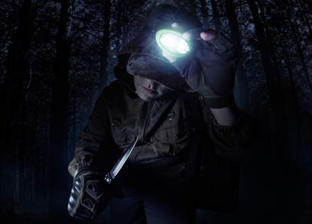 Foto per Profile view photo of a male person in brown tactical outfit jacket, gloves and knife turning on head flashlight on night woods background. - Immagine Royalty Free