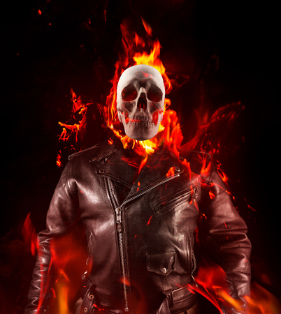 Photo for Photo of a demon skeleton in black leather biker jacket torso view standing in fire on black background. - Royalty Free Image