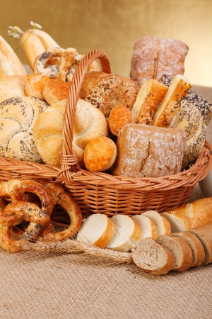 Photo pour Composition of various baked products in basket on rustic background - image libre de droit