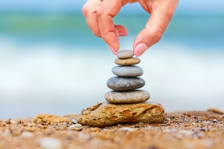 Photo for Hand placing the last pebble of a stacked tower on the sea side - Royalty Free Image