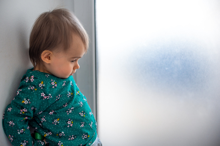 Photo for Cute caucasian one year old baby girl in green shirt standing with back against wall next to bright window. Copy space on right - Royalty Free Image