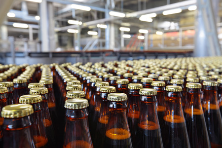 Foto de The food industry. Glass beer bottles moving on conveyor - Imagen libre de derechos