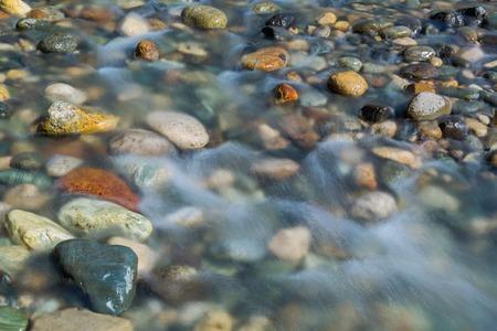 Foto de Pebble stones in the river water close up view, natural background - Imagen libre de derechos