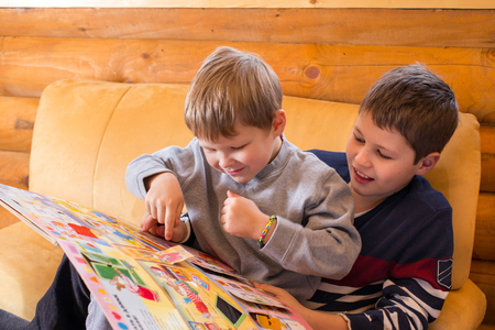 Younger brother learning to read with help of elder one