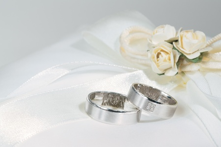 Foto de Wedding rings on a white sating ring bearer pillow with flowers. - Imagen libre de derechos