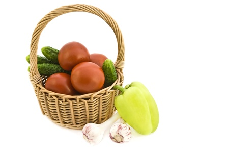 Basket with fresh ripe vegetables on white background .