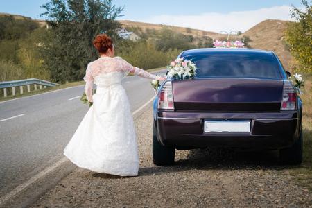 Foto de bride and car, bride in a white dress with a bouquet near the wedding car - Imagen libre de derechos