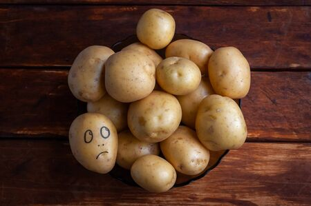 Photo for a potato with a painted face lies on a plate. concept of dissent rejection and loneliness - Royalty Free Image