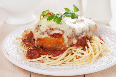 Foto de Parmesan chicken with melted cheese and tomato sauce served over spaghetti pasta - Imagen libre de derechos