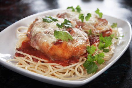 Foto de Chicken parmesan with melted cheese and tomato sauce served over spaghetti pasta - Imagen libre de derechos