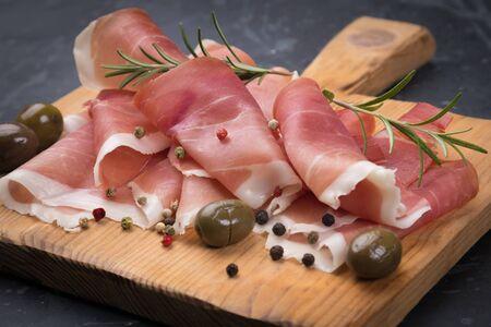 Foto de Slices of cured ham similar to italian prosciutto or spanish jamon iberico - Imagen libre de derechos