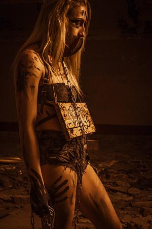 Foto de Miserable pretty slave with chain posing over ruins - Imagen libre de derechos