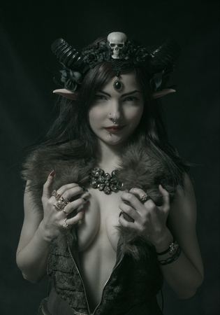 Photo for Pretty girl with horns and elvish ears posing over dark background - Royalty Free Image