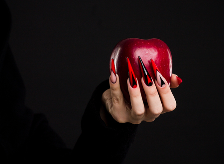 Photo for Hands with scary nails manicure holding red apple , isolated on black background - Royalty Free Image