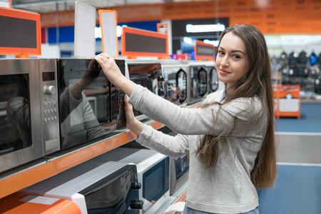 Foto de customer girl chooses a microwave oven in a home appliance store - Imagen libre de derechos
