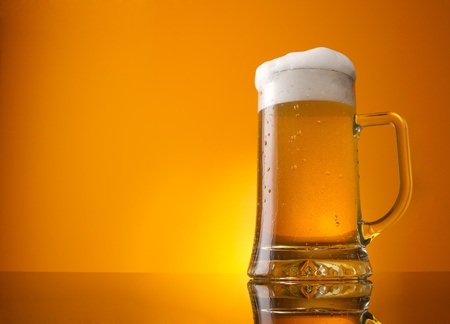 Photo pour Glass of beer close-up with froth over orange background - image libre de droit