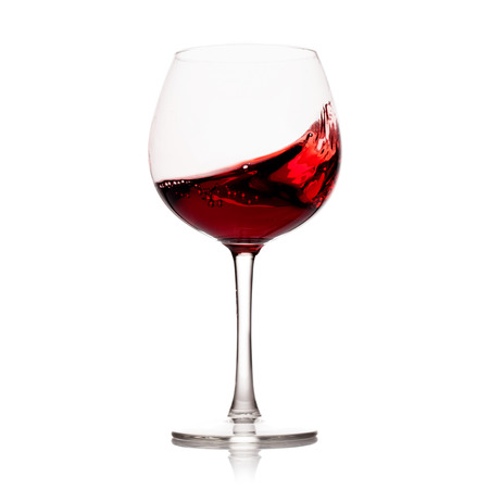Photo pour moving red wine glass over a white background - image libre de droit