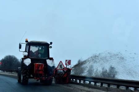Photo pour Tractor removes snow winter - image libre de droit