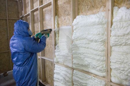 Foto de Worker insulates with a special foam wall - Imagen libre de derechos