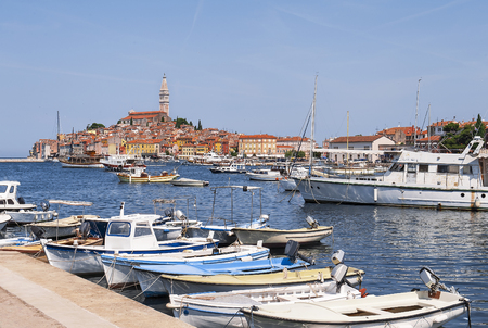 Photo pour Old center harbor with fishing boats during a summer day. Wonderful romantic bright view of the medieval Rovinj, Croatia, Istria.  A picturesque town with colorful houses and characteristic church - image libre de droit