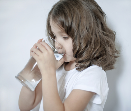 Photo pour Child drinking clean water at home, close up. Little cute girl holding water glass in her hand. Taking care of own health. Concept of healthy lifestyle, good habit - image libre de droit