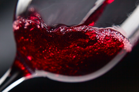 Photo pour Red wine in wineglass on  black background - image libre de droit
