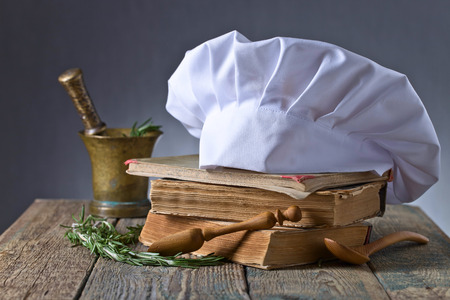 Foto de Old copper mortar with rosemary. Culinary books , chef hat and wooden spoons . Kitchen accessories on the old wooden table . - Imagen libre de derechos