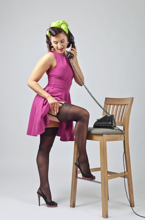 Photo pour Beautiful brunette woman in pin up style with perfect hair and make up speaking via vintage phone.Expressive facial expressions. - image libre de droit